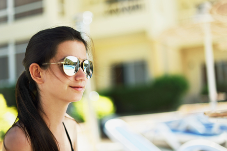 pretty smiling girl sitting a poolside. swimming pool and the hotel building are reflected in her sunglasses