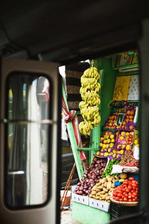fruit shop on the streets of Egypt. view through the open doors of a tourist bus. vertical