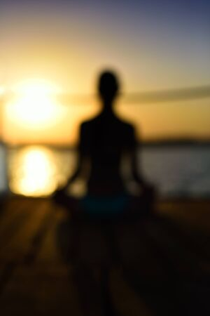 blurred image back woman sitting in a lotus pose on the wooden planks, sunset, vertical Stock Photo
