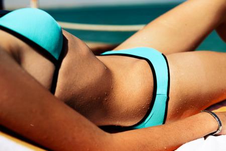 slim girl sunbathing on the beach close-up, horizontal
