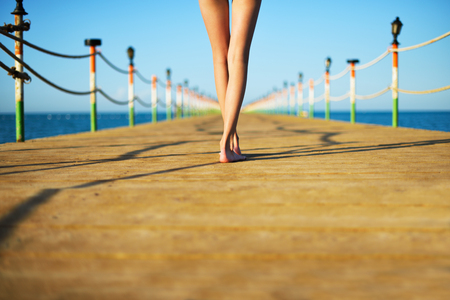 young womans legs on a bridge in the sea Stock Photo