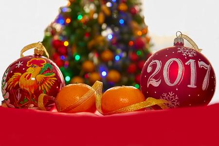 two Christmas ball and mandarins on the Christmas tree