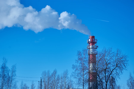 horizontal image of red and white chimney in the background of clear sky Stock Photo