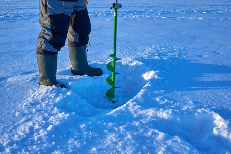 the fisherman makes a hole in the ice of the lake Stock Photo