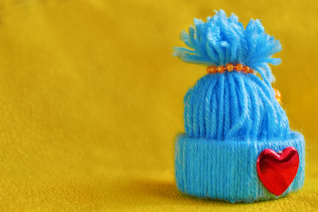 blue knitted hat with a heart on a yellow background