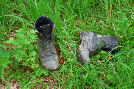 Old leather boots lying in the grass