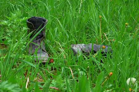 old leather boots lying in the grass Stock Photo