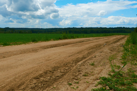 the road disappears in the distance among fields and forests Stock Photo