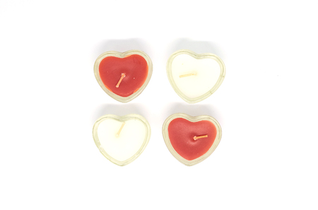 four heart shaped candles isolated on white background