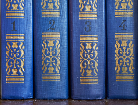 the pattern on the covers of four volumes of old books close-up