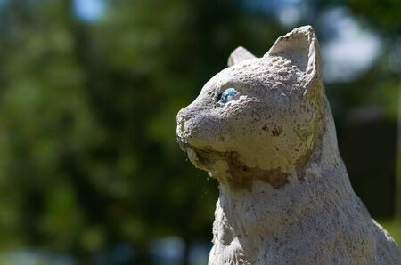 old shabby statue of a cat close-up against the green foliage of trees Stok Fotoğraf - 132388742