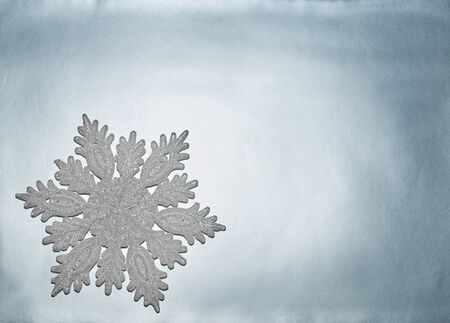 Decorative snowflake lies on a silver background