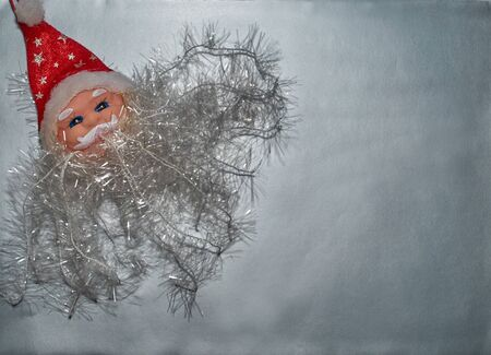 Decorative figure of Santa Claus lies on a silver background Stock Photo