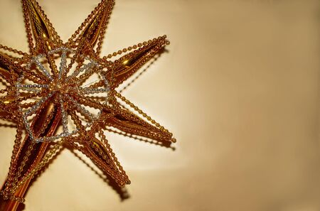 Christmas star made of gold colored glass lies on a gold background 写真素材