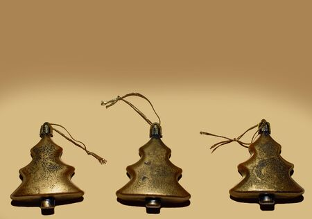 A set of Christmas tree toys lies on a gold background