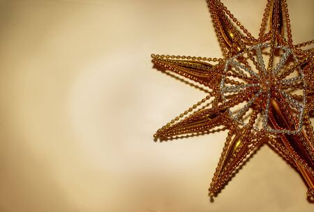 Christmas star made of gold colored glass lies on a gold background Stok Fotoğraf - 132389153