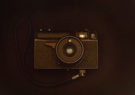 old film camera with strap close-up on brown background Stok Fotoğraf - 132389158
