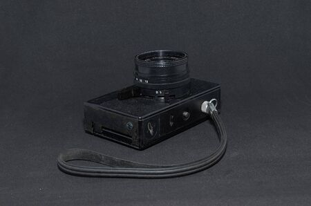 old film camera with strap close-up on black background