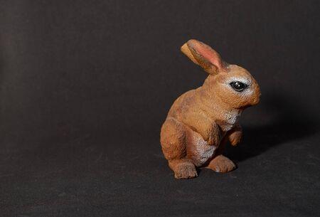 plaster figure of a hare on a black background Archivio Fotografico - 132120158
