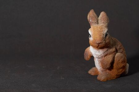 plaster figure of a hare on a black background Archivio Fotografico - 132120482