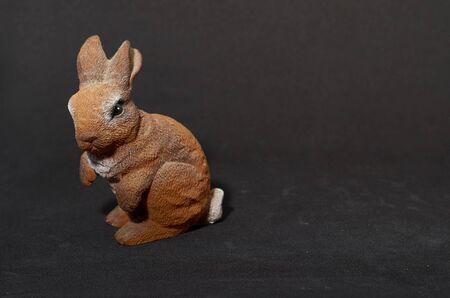 plaster figure of a hare on a black background Stok Fotoğraf - 132119361