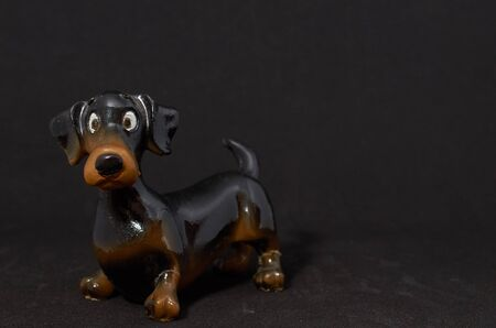 ceramic figurine of a dog Dachshund close-up on a black background Archivio Fotografico - 132389161