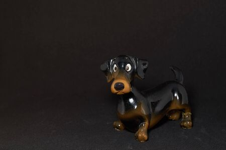 ceramic figurine of a dog Dachshund close-up on a black background