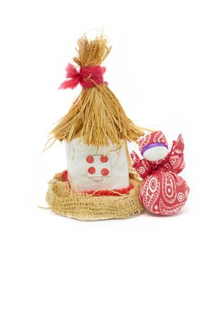 A statuette of a village house with a thatched roof and a rag doll isolated on a white background handmade
