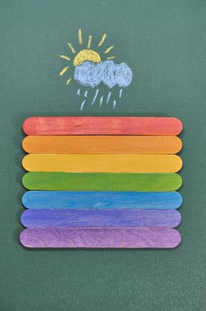 Planks painted in seven colors of the rainbow on the background of a chalk Board and a chalk drawing of a cloud and the sun. Flat lay Stok Fotoğraf