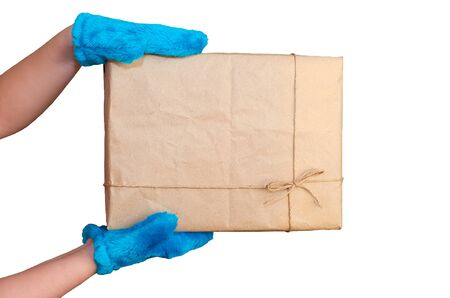 the childs hands in blue mittens hold a rectangular cardboard box with a gift isolated on a white background Stok Fotoğraf