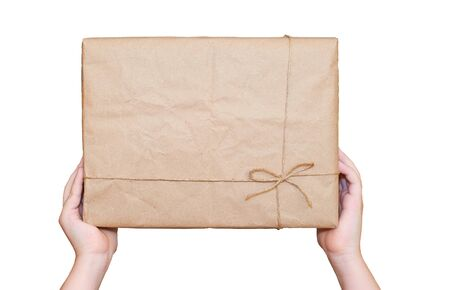 childs hands hold a rectangular cardboard box with a gift isolated on a white background Stok Fotoğraf