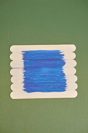 a background of planks painted white and blue lies on a chalk Board