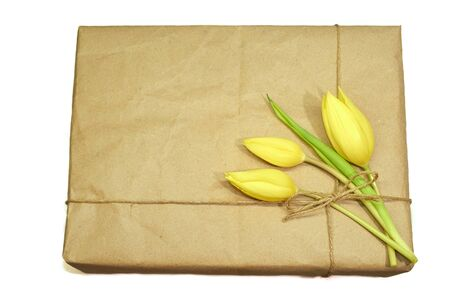 three yellow tulips tied with a rope to a cardboard box flat lay