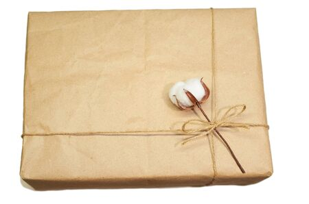 one white artificial cotton flower is tied with a rope to a cardboard box flat lay