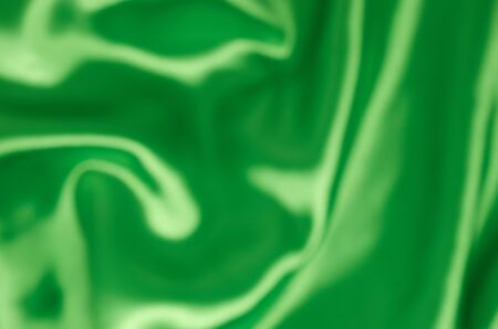 Blurred background of satin green fabric in pleats
