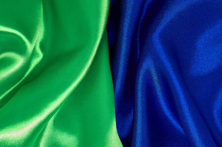 Background of green and blue satin fabric in pleats