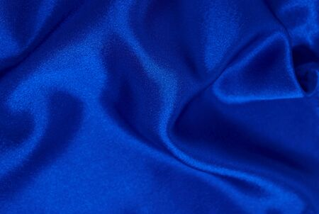 Background of blue satin fabric in folds horizontal format