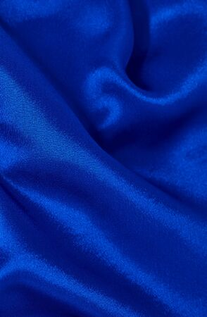 Background of blue satin fabric in folds vertical format