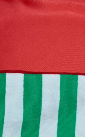 background of red satin fabric and knitted scarf with white and green stripes vertical format