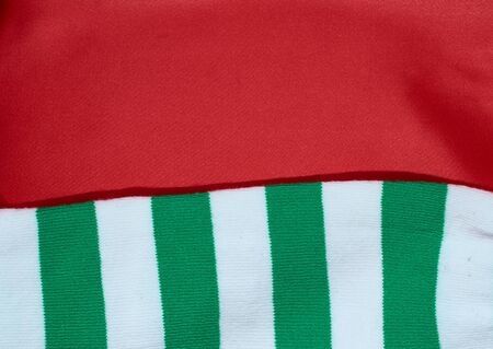 background of red satin fabric and knitted scarf with white and green stripes Stok Fotoğraf