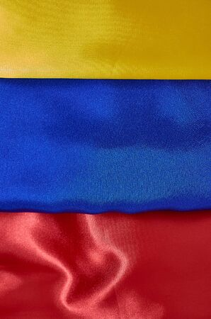 background of red, blue, yellow satin fabric with pleats