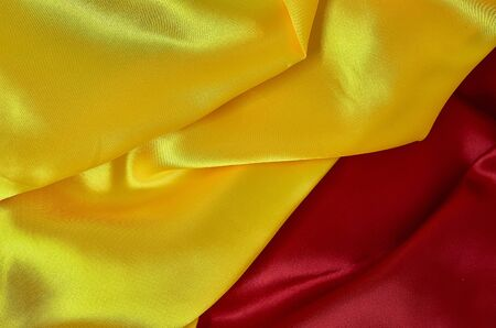 background of red, yellow satin fabric with pleats