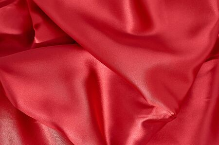 Background of red satin fabric in folds horizontal format