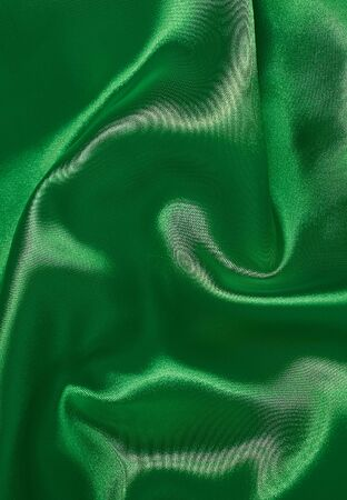 background of satin green fabric in pleats vertical format