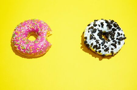 Pink and white donuts lie on a yellow background. The view from the top Banco de Imagens