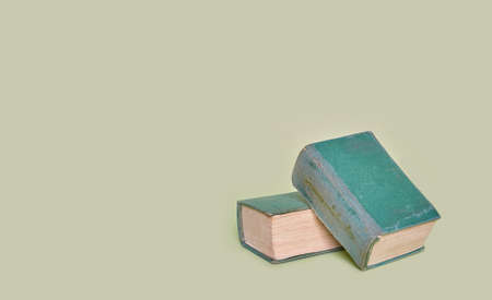 Two old books lie on a plain green background. Banner Zdjęcie Seryjne