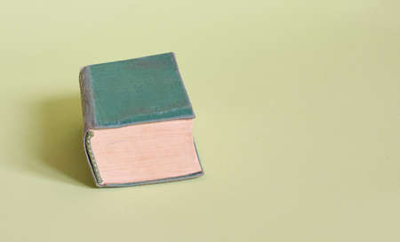 The old green book lies on a plain green background. Close up