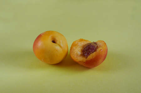 Whole and bitten nectarines lie on a colored background. Close up