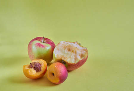 Whole and nibbled apples and nectarines lie on a colored background. Close up Stok Fotoğraf