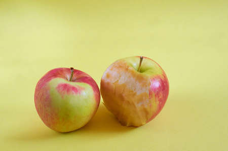 A whole Apple and a bitten Apple lie on a colored background. Close up